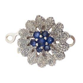 Der hübsche blütenförmige Perlkettenverschluss ist mit einem zarten Dekor versehen. Mittig zieren 7 Saphire das Schmuckstück.